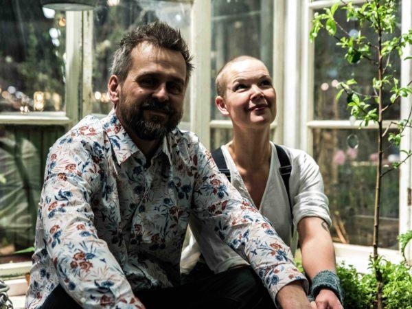 Johannes och Sara sitter framför ett växthus. Johannes har blommig skjorta och Sara har vit skjorta och svarta hängslen.