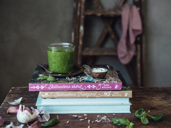 En härligt, grön pesto står i en glasburk på böckerna Skillnadens Trädgård och Skillnadens Skörd.