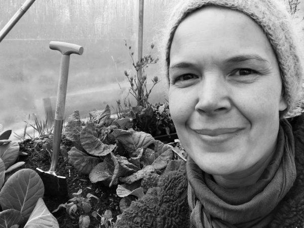 Svartvit bild av Sara i tunnelväxthuset. Bakom syns en liten spade och stora buckliga bladkål.