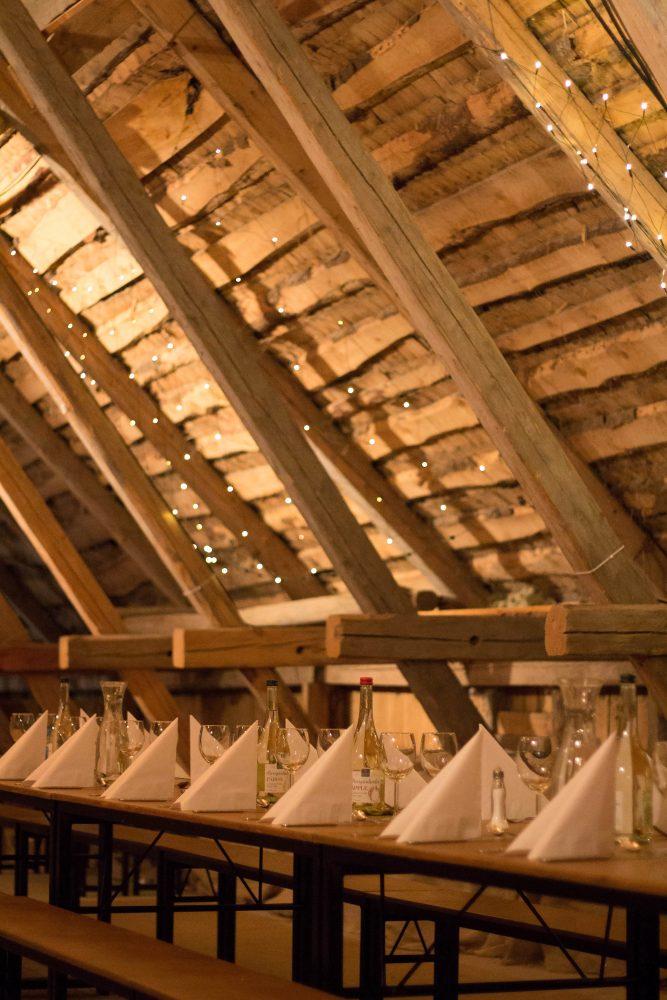 Logen på Rinkabygård med ljus, glittrig belysning på de bara träväggarna och dukning med höga glas och krispiga servetter på borden.