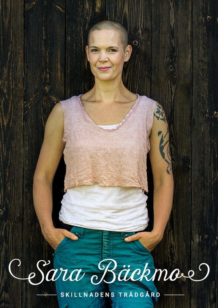 Sara står mot en märkgrå trävägg, i ett vitt och ett rosa linne, blå arbetsbyxor och en glad med bestämd blick..