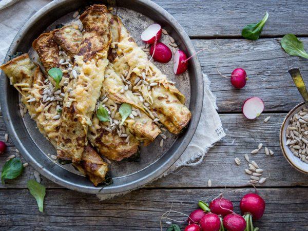 En tallrik där det ligger crepes i en hög. På dem syns smält ost och runt omkring ligger det illrosa rädisor på ett grått träbord.