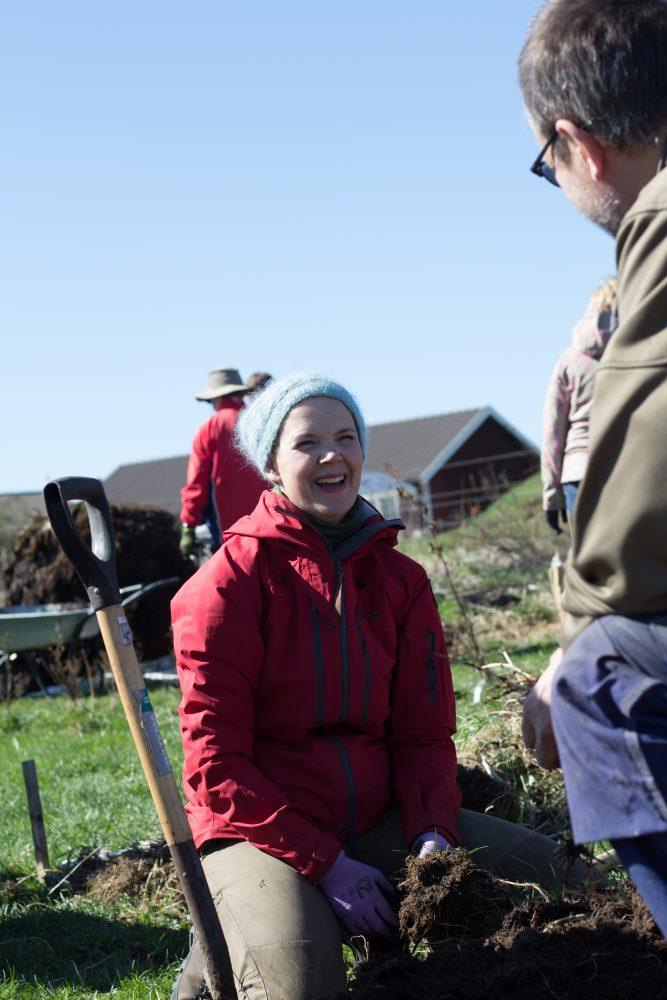 Sara skrattar. Hon sitter ner i köksträdgården och tittar mot en kursdeltagare som har ryggen till kameran.