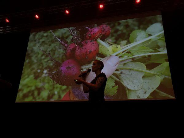 Sara Bäckmo håller föredrag på scen.