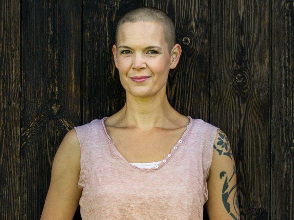 Närbild av Sara, i ett rosa linne framför en mörkgrå trävägg.