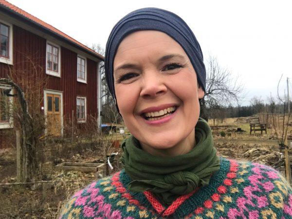 Sara Bäckmo i fägglad tröja ute i köksträdgården.