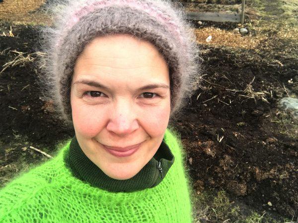 sara står i grön stickad tröja och toppluva i trädgården som är snöfri.