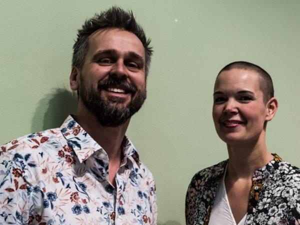 Johannes och Sara står bredvid varandra vid en grå vägg. Båda har mönstrade kläder.