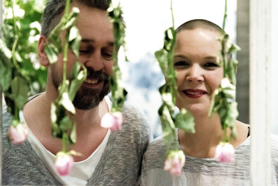 Johannes och Sara står bakom en skir garden av rosa blommor.