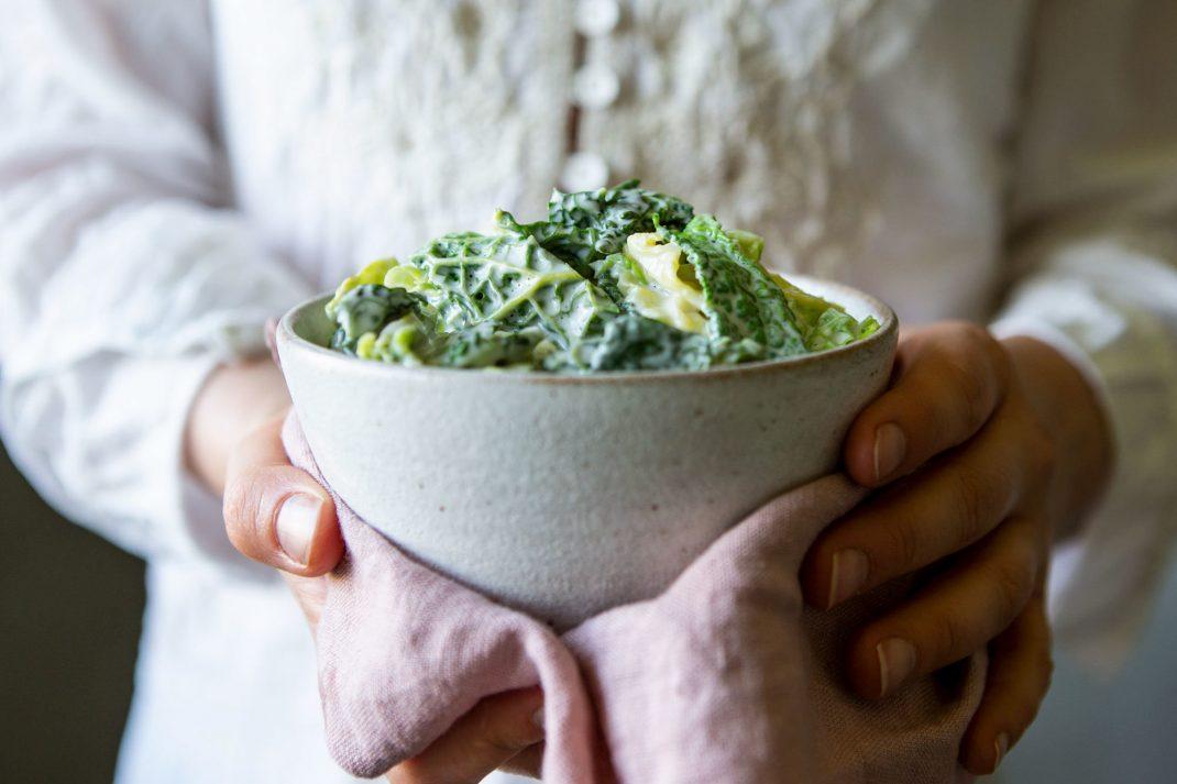 En keramikskål fylld med stuvad kål i pudriga gröna nyanser lyfts fram av två händer.
