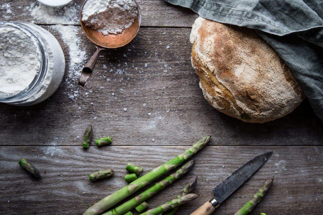 Ett rustikt bröd ligger på ett träbord tillsammans med sparris och mjöl.