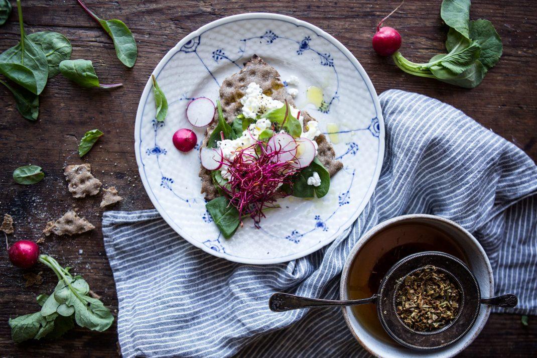 På ett träbord står en tallrik med ett knäckebröd fyllt av krispiga bladgrönsaker och keso. Bredvid står en kopp te.