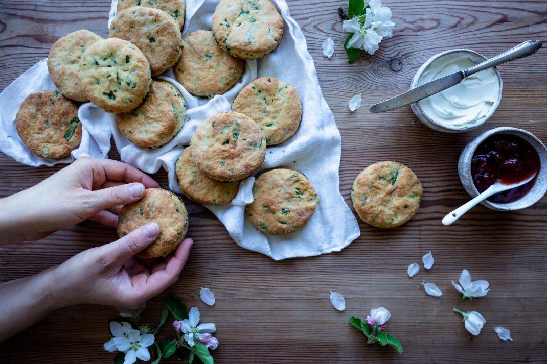Runda, gyllene bröd med strimlor av grönt ligger över en vit bakduk på ett bord medan två händer plockar till sig en bit.