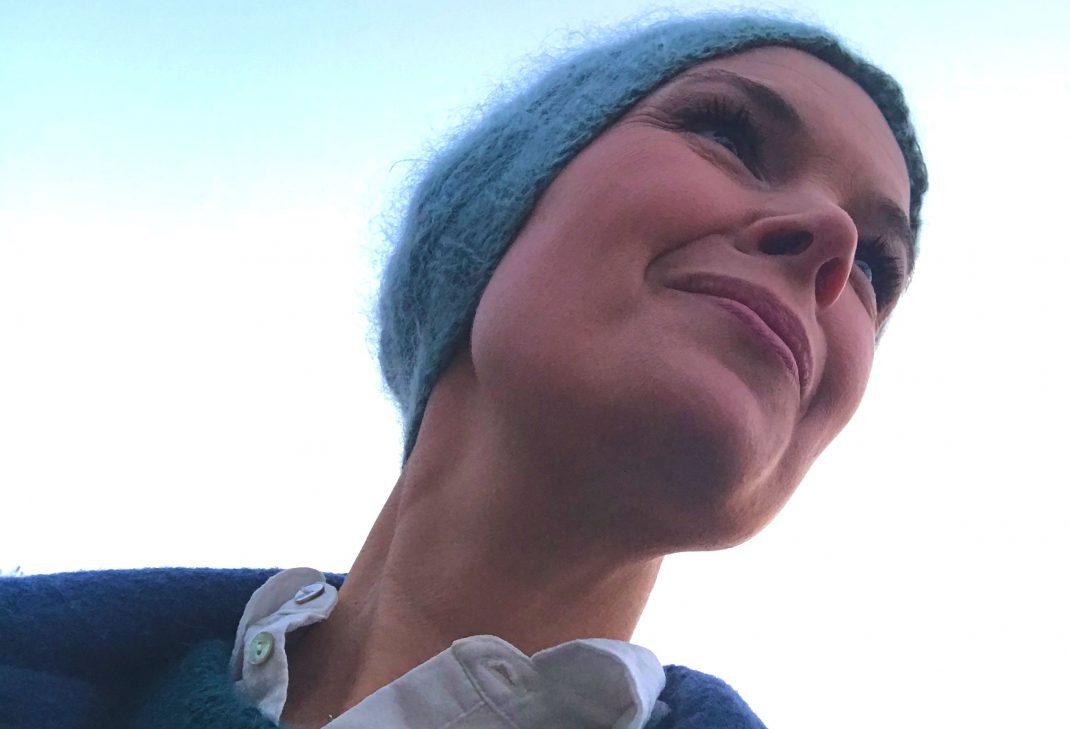 Sara Bäckmo fotograferad underifrån, tittar ut över himlen.