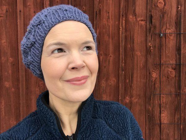 Sara Bäckmo står längs en röd husvägg
