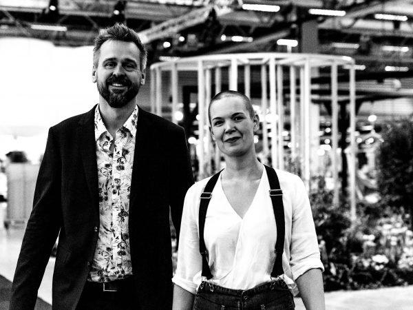 Ett svartvitt foto av Johannes och Sara framför ett växthusliknande bygge.