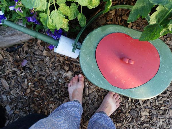Saras brunbrända fötter bredvid en grön vattenkanna med hjärtformat lock och en toapappersrulle om pipen.