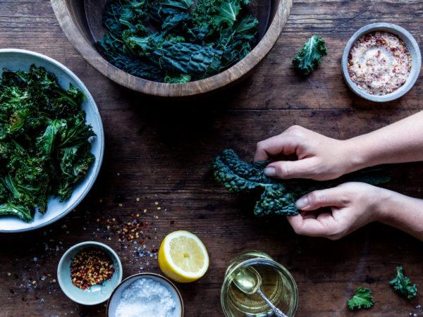 På ett mörkt träbord syns skålar med knallgröna kålblad, olja, salt och kryddor plus två händer som knådar ett kålblad.