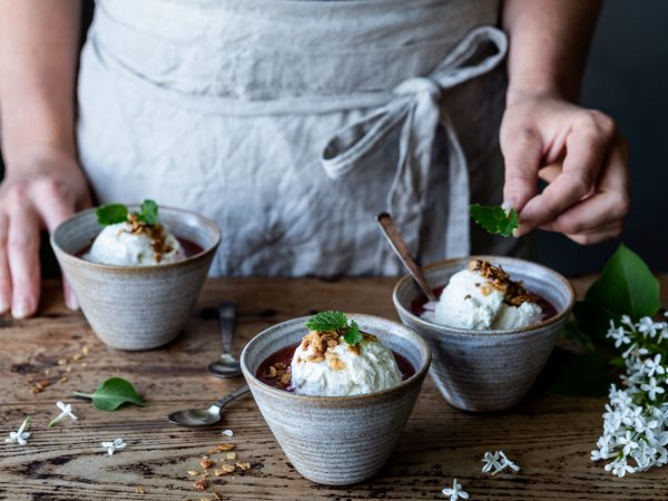 På ett bord står det uppdukat skålar med glass och rabarbersås, citronmeliss och syrenblommor.