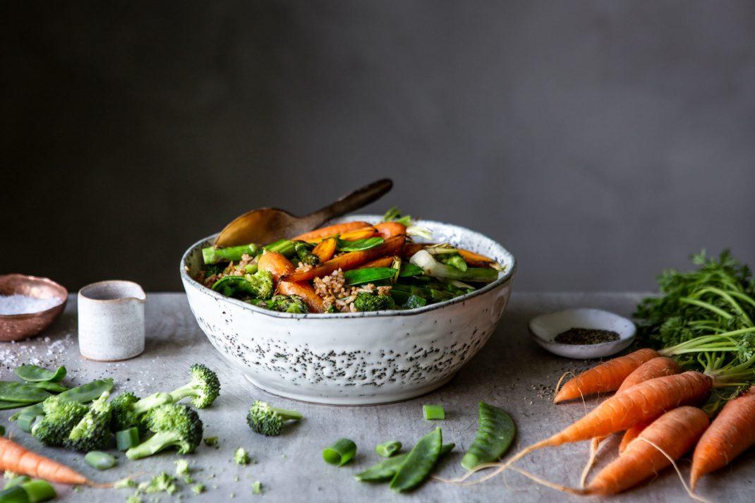 Stekt ris i en skål med massor av krispiga grönsaker. Morötter och broccoli ligger runt om.