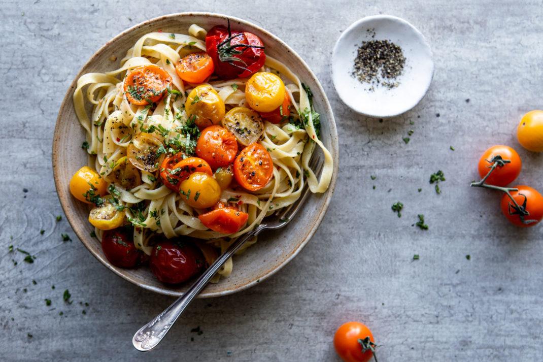 En tallrik med stekta små tomater och pasta.
