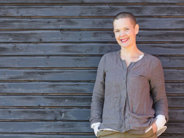 Sara mot en grå ladugårdsvägg med ett stort leende på läpparna.