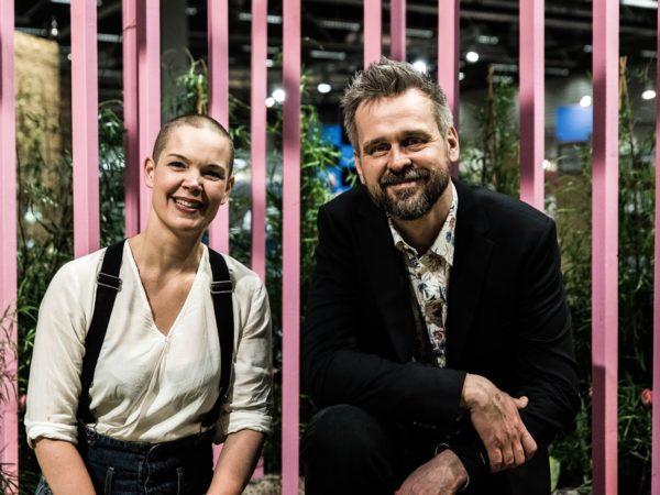 Bild på Sara och Johannes som skrattar framför en bakgrund med rosa stolpar.