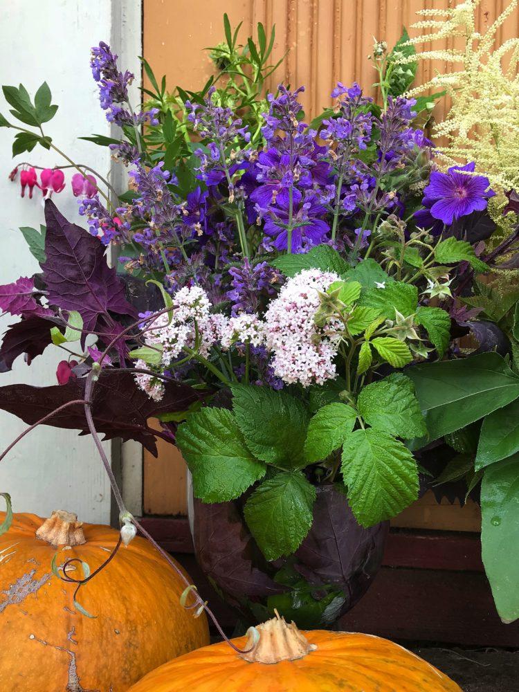 En färgglad blomsterbukett bredvid gula pumpor.