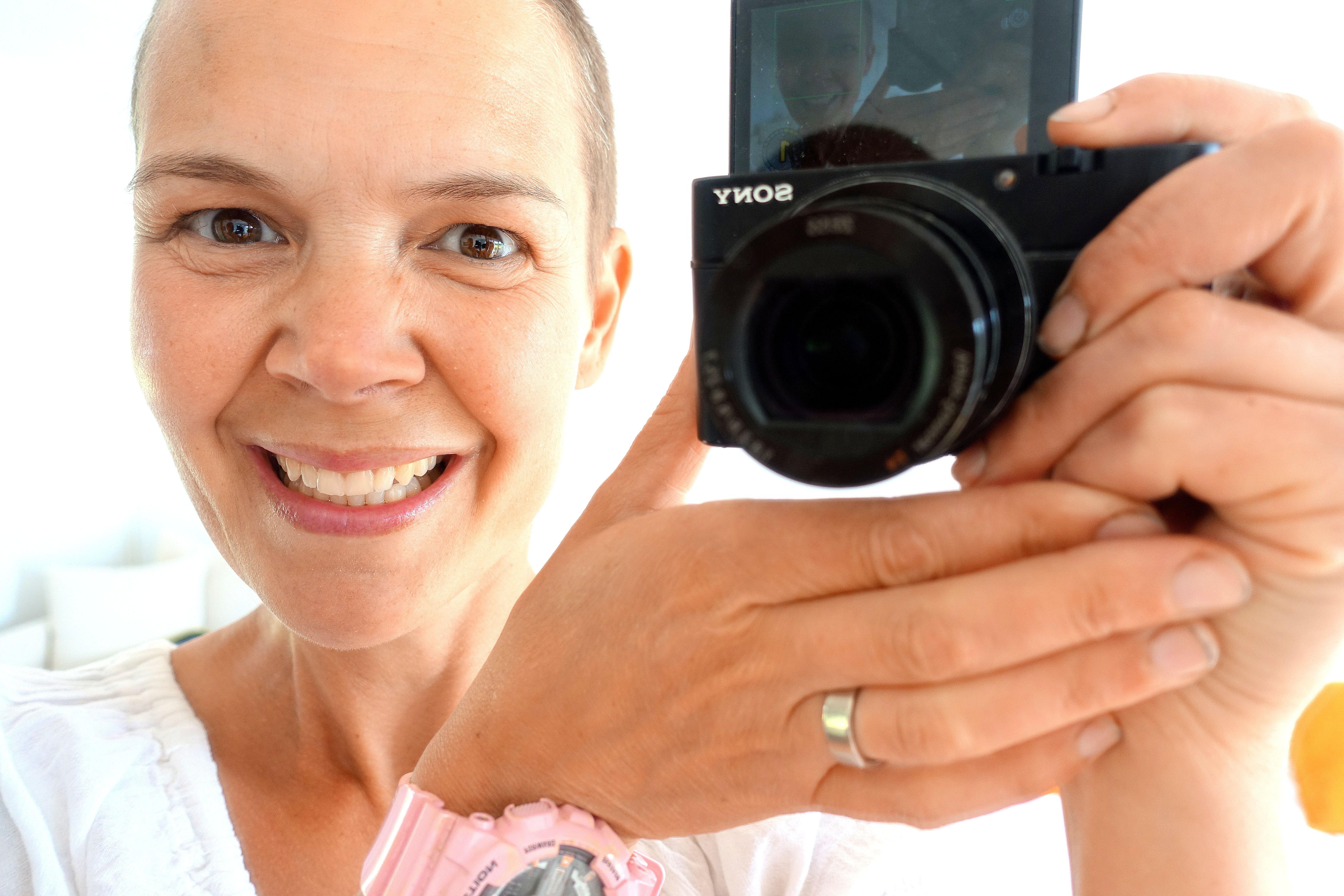 Sara tar en selfie genom en spegel, och både hon och kameran syns i bild.