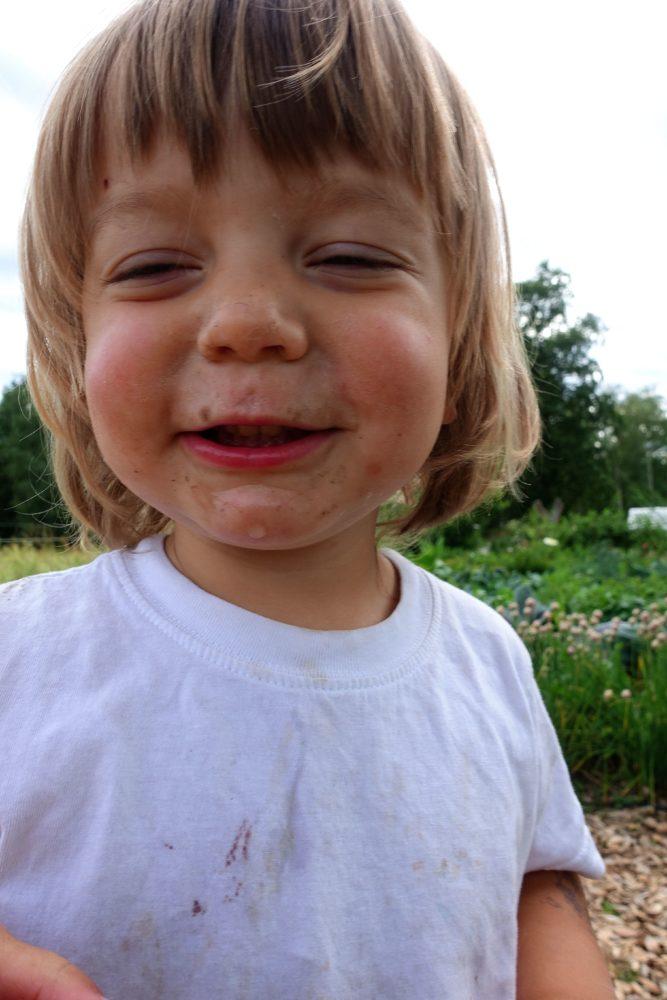 Ett glatt barn, smutsigt i ansiktet.