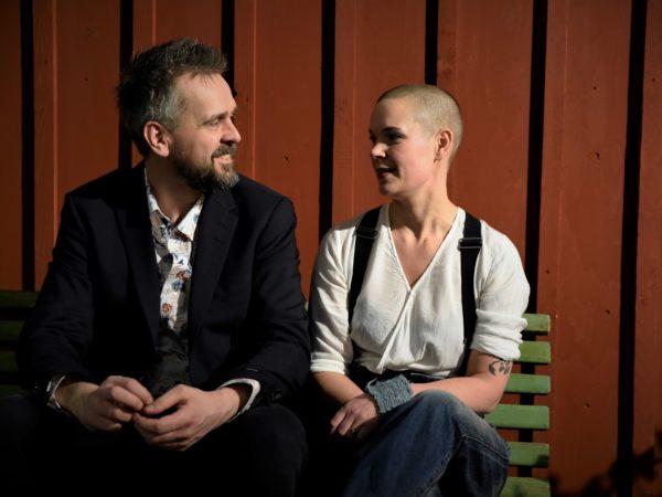 Johannes och Sara sitter bredvid varandra framför en röd vägg.
