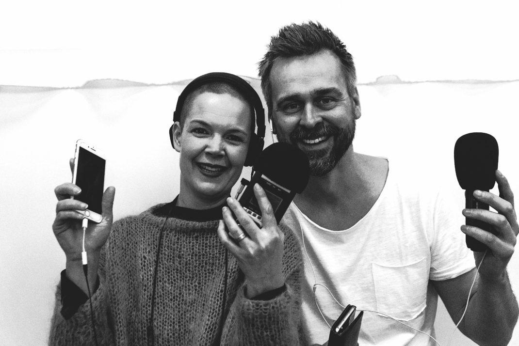 Sara och Johannes i svartvitt fotot, hållandes sina telefoner med diverse sladdar.