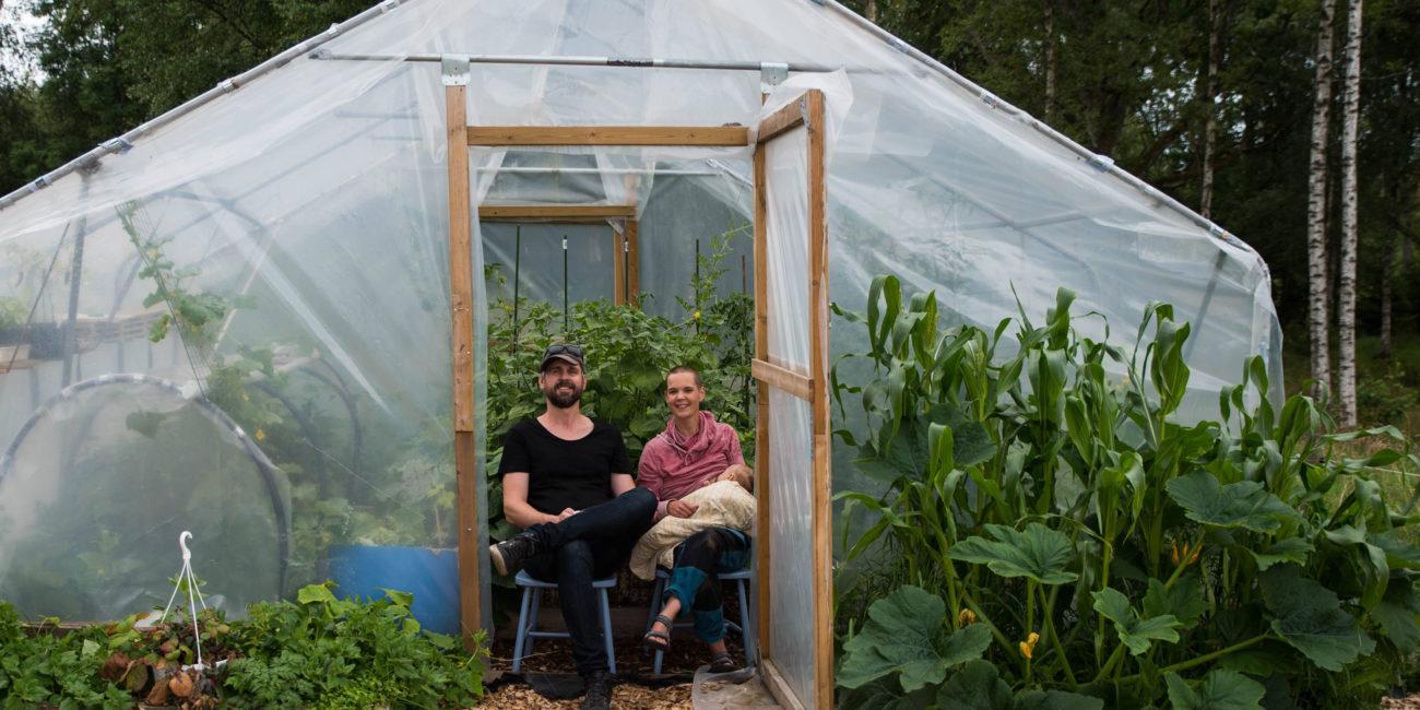 Johannes och Sara sitter i öppningen till Saras tunnelväxthus.