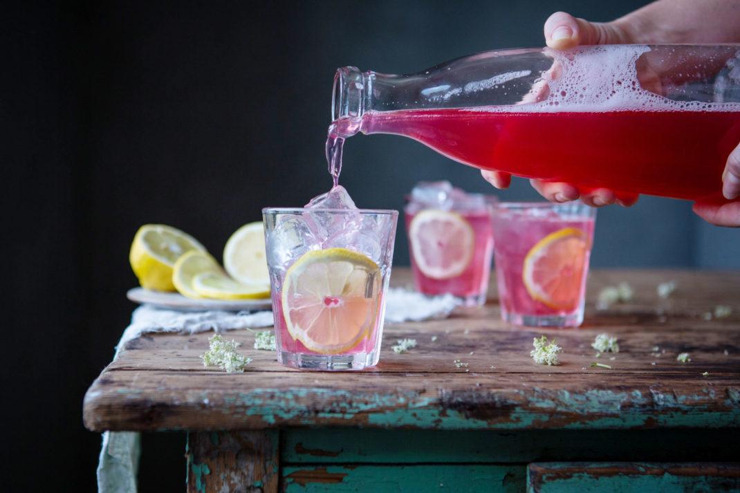 I ett mörkt rum häller någon upp en rosaröd dryck i ett glas fullt med is och citroner.