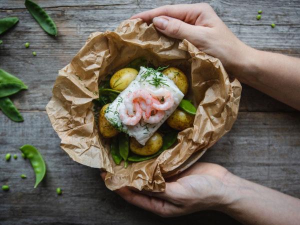 I en knyte av bakplåtspapper ligger gyllengul potatis, krämig, vit fisk och sockerärtor.