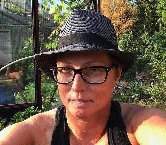 En selfie på kvinna i hatt i en trädgård.