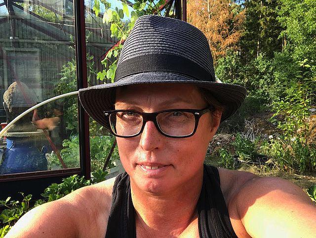En selfie på kvinna i hatt i en trädgård. Mulching works, Anna Skog Pettersson.