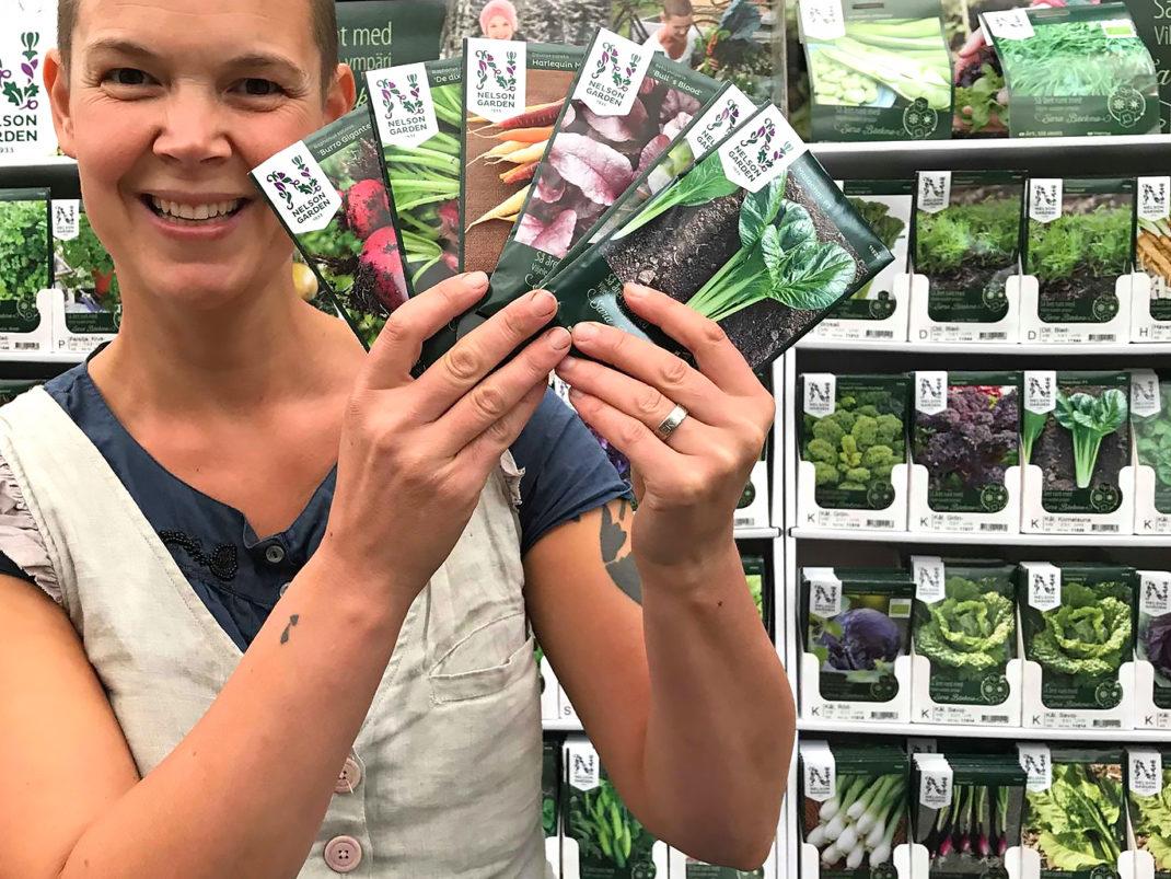 Sara står med fem fröpåsar framför ett ställ med hundratals fröer. Hon ser väldigt glad ut.