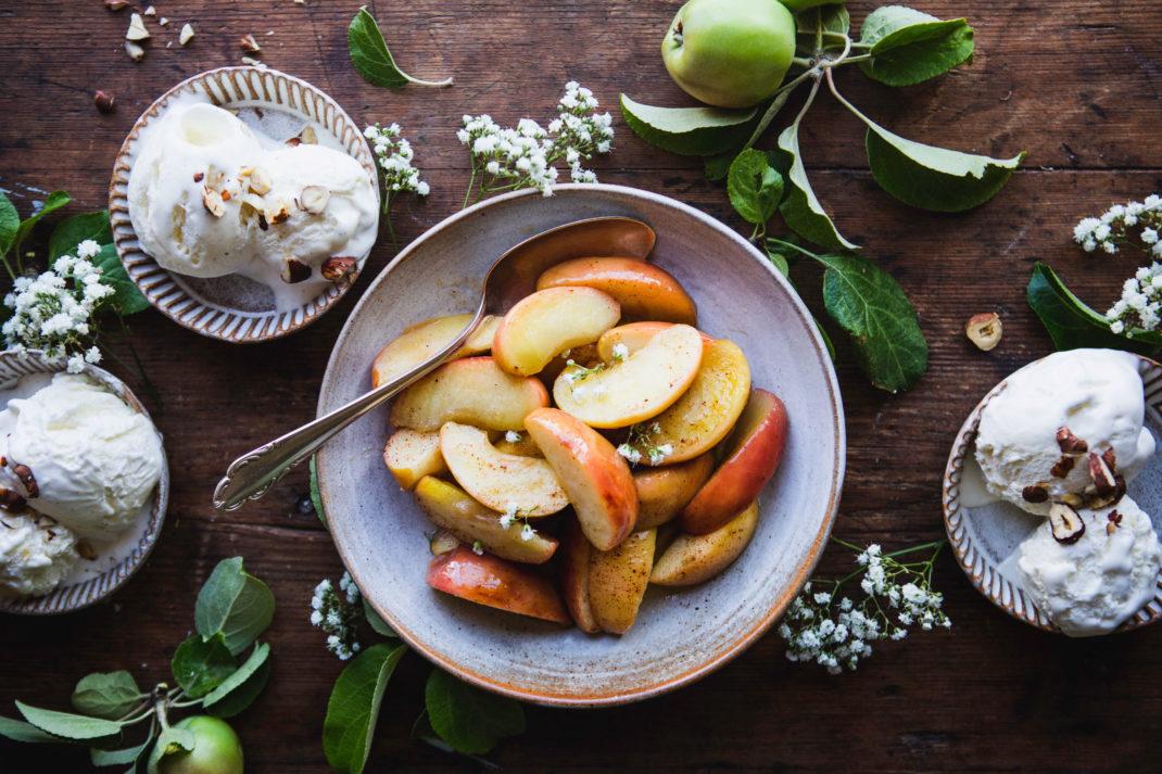 Gyllengula äppelklyftor med rosaorange skal ligger i en tallrik, runt om står skålar med glass.