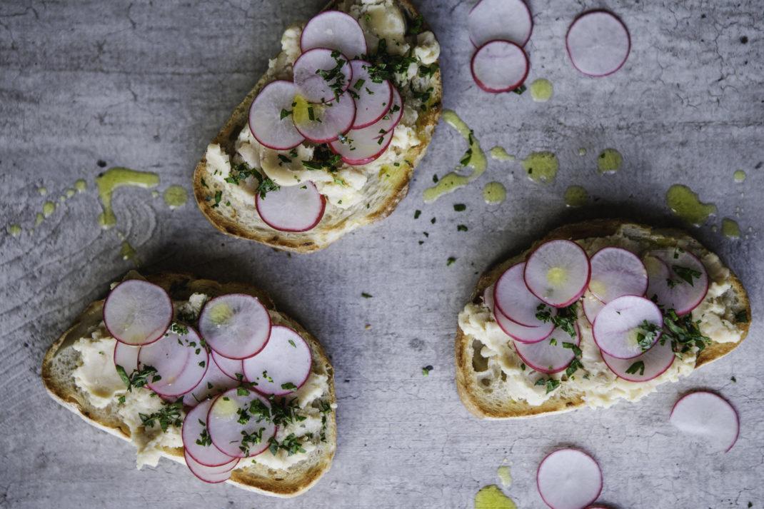 Tre smörgåsar med ljus bönröra och skivad rädisa.