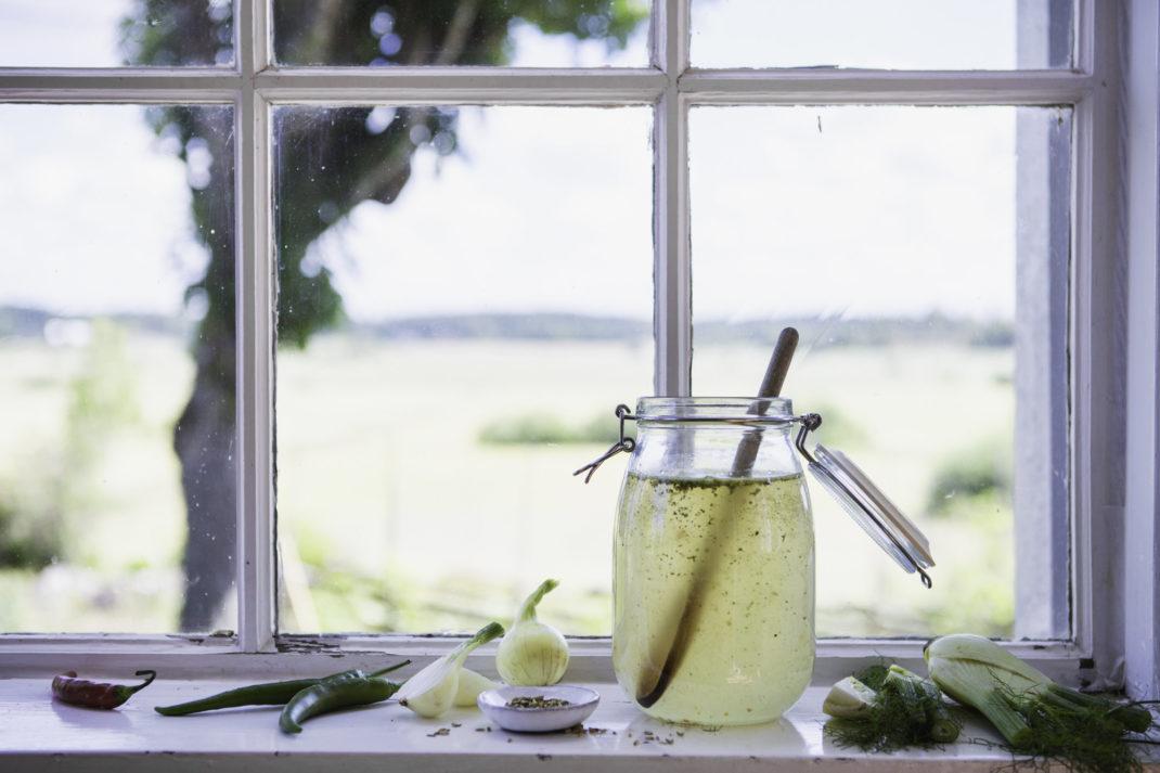 En glasburk med ljusgul buljong står i en fönster som vätter ut mot öppna fält.