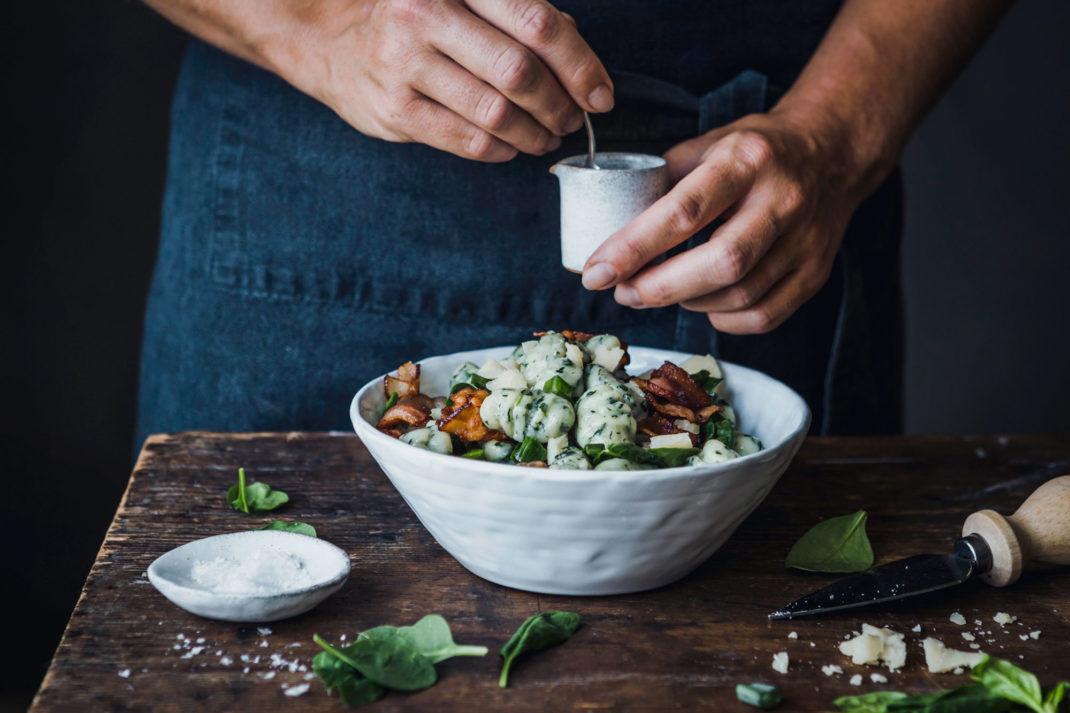 Två händer, ett mörkblått förkläde och ett bord med en tallrik full av gnocchi och grönsaker.