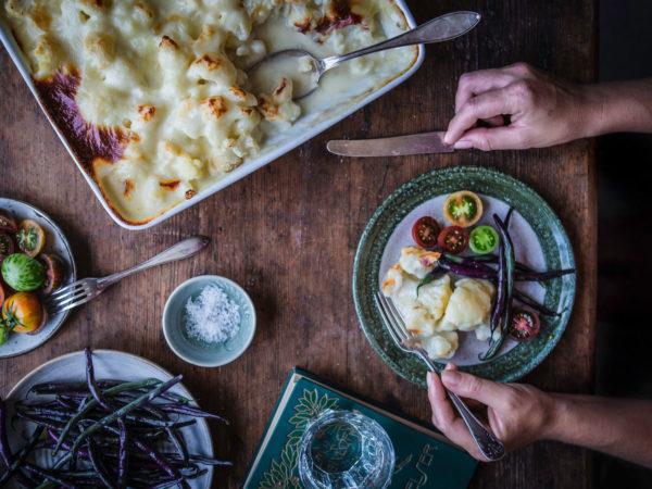 En vit gratäng, en skål med bönor i mörkgrönt och lila, en skål med tomater i olika färger. Och ett par händer som hugger in på måltiden.