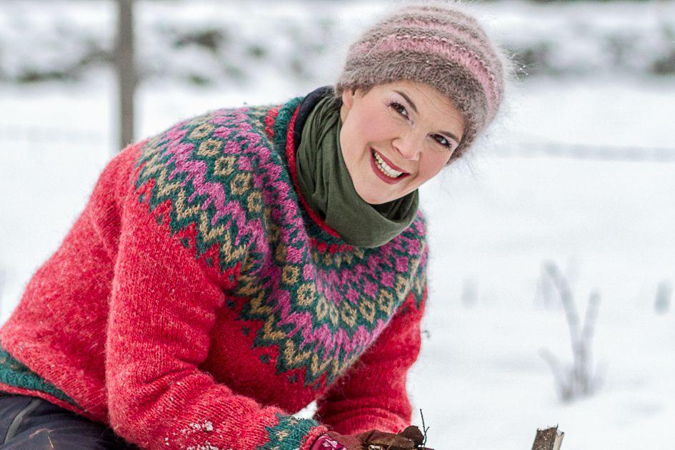 Sara Bäckmo i färgglad tröja och stort leende i snön.