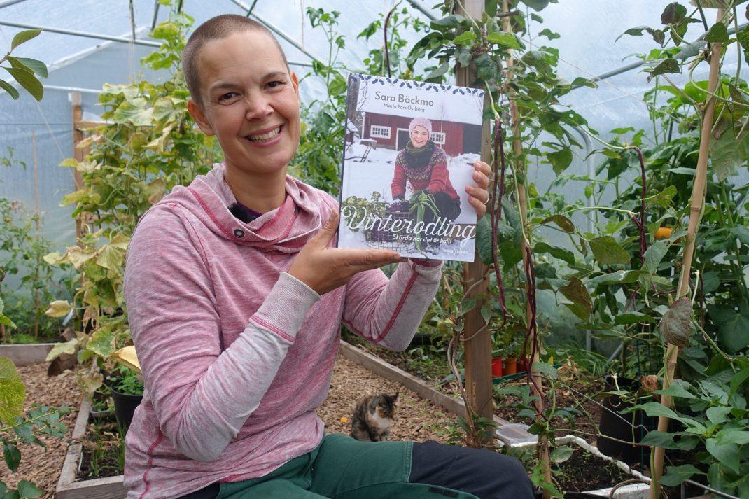 Sara Bäckmo sitter i växthuset och håller den nya boken bredvid sig.