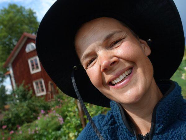 Bild på Sara med bostadshuset i bakgrunden. Sara har en svart hatt på sig.