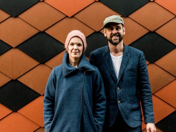 Sara och Johannes står framför en orange- och svartaktig vägg .