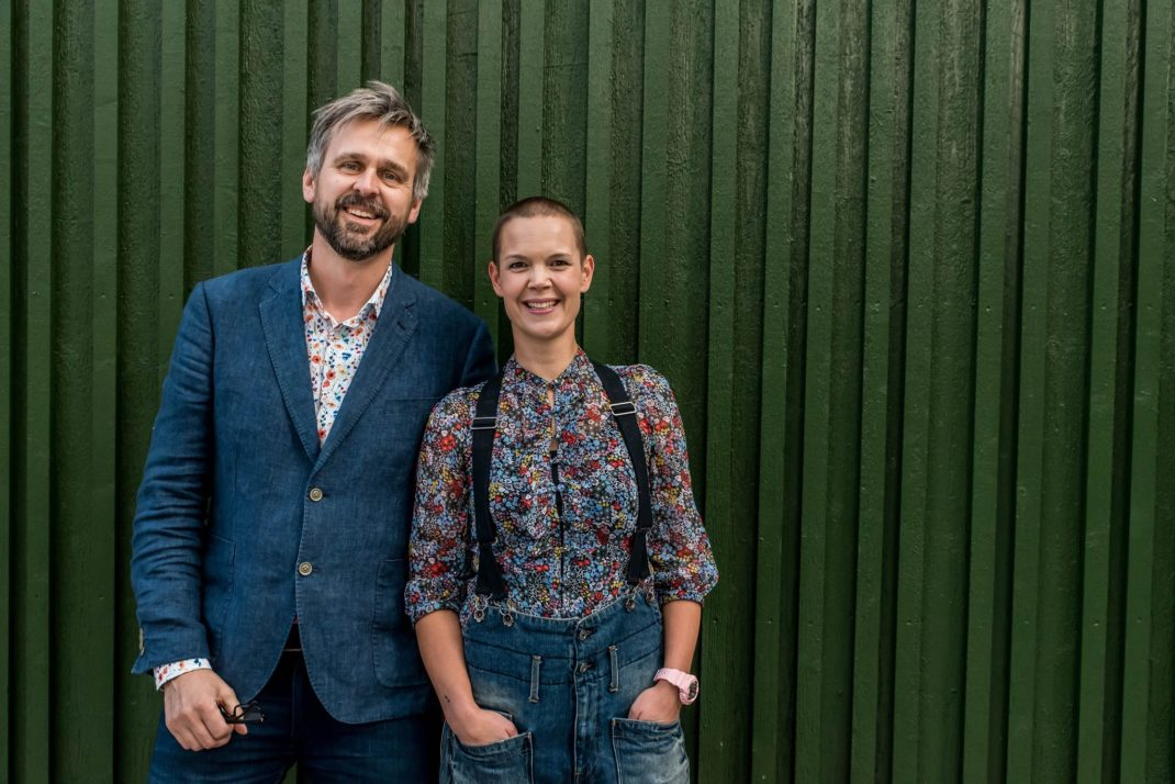 Sara och Johannes står framför en mörkgrön vägg och ler mot kameran.