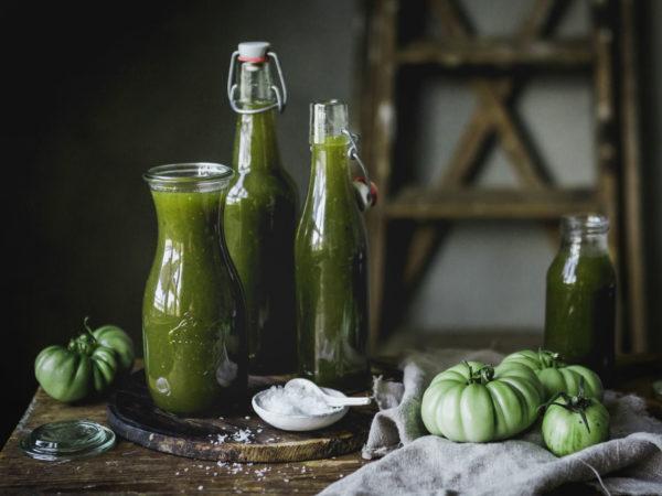I en vacker miljö med träbord och en rustik trästege står ett antal flaskor med grön ketchup i. På bordet ligger stora gröna tomater som nästan ser ut som minipumpor.