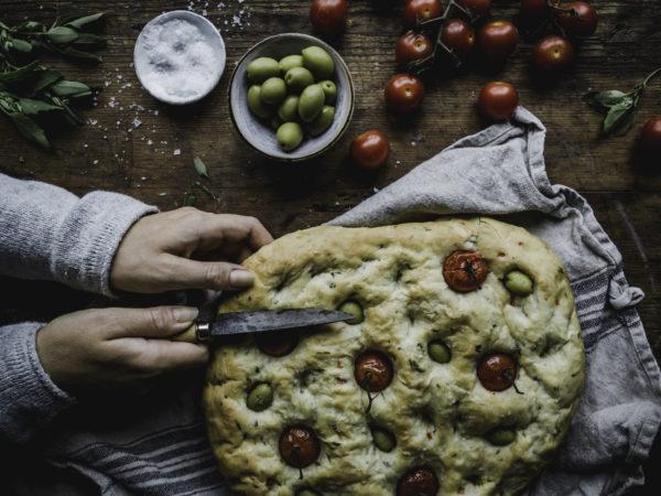 Två händer skär upp ett fantastiskt, platt bröd med tomater i.